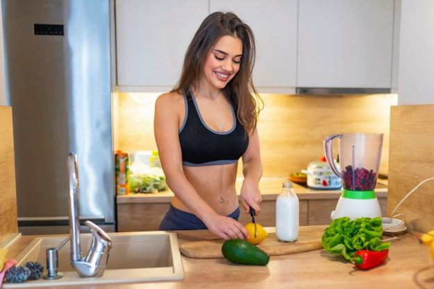 happy woman slicing fruits for her smoothie