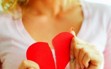 woman holding a torn apart heart