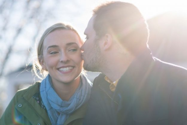 A guy kissing a girl on the cheek
